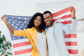 african american couple holding flag of america