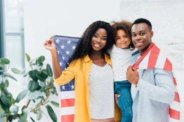 African american family holding flag of america and looking at camera stock vector