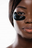 cropped view of african american woman with hydrogel eye patches on face isolated on white