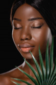 Afričanky americká nahá žena se zavřenýma očima a zeleným palmovým listem izolované na černé
