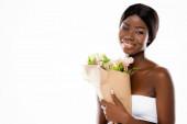 africká americká žena s úsměvem při držení kytice květin izolovaných na bílém