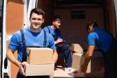 A kartondobozokat tartó és a kamerába néző fiatal rakodó szelektív fókusza, miközben a kollégák a szabadban rakodják ki a teherautót