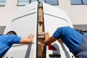 Nízký úhel pohledu na stěhováky zavírání dveří kamionu s lepenkovými krabicemi na městské ulici