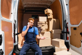 Loader talking on smartphone while sitting near packages in truck outdoors