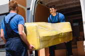 Selective focus of movers unloading sofa in stretch wrap in truck outdoors