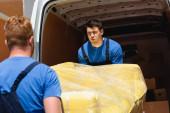 Fotografie Selektivní zaměření unaveného nakladače nesoucího gauč v natahovacím zábalu se spolupracovníkem v blízkosti kamionu s otevřenými dveřmi venku