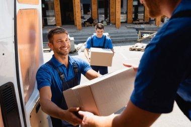 Selective focus of loader giving carton box to colleague in truck on urban street stock vector