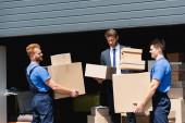 Magabiztos üzletember csomagokat tart a költöztetők és a raktár közelében a szabadban
