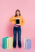 vzrušená žena ve žluté bundě drží digitální tablet v blízkosti barevných nákupních tašek na růžovém pozadí