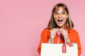 Vzrušená žena v slunečních brýlích drží nákupní tašky s prodejem slovo na cenovky izolované na růžové