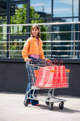 Young woman looking away while walking near cart with shopping bags on urban street
