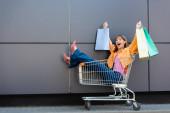 vzrušená žena v podpatcích drží barevné nákupní tašky, zatímco sedí v košíku v blízkosti budovy