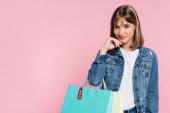 Mladá žena v džínové bundě při pohledu na kameru při držení nákupních tašek s cenovkou na růžovém pozadí
