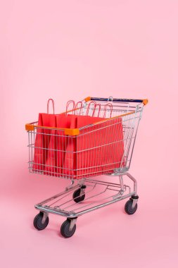 Red shopping bags in trolley on pink surface stock vector