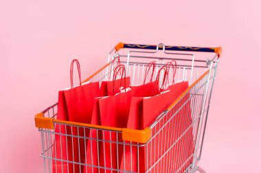 Red shopping bags in cart on pink background stock vector