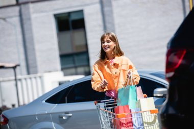Selective focus of woman holding shopping bags near cart and cars on parking stock vector