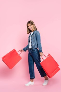 Young woman in jeans and denim jacket looking at camera while holding shopping bags on pink background stock vector