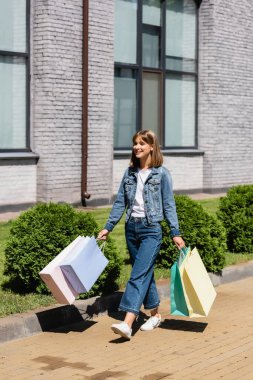 Young woman in denim jacket holding shopping bags while walking on urban street stock vector