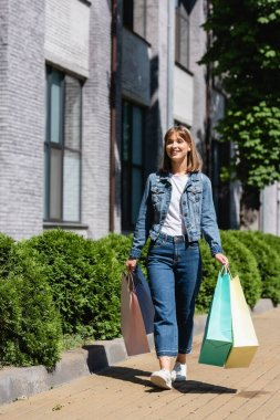 Woman in jeans and jacket holding shopping bags while walking on urban street stock vector