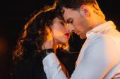 Mann berührt lockige Frau mit geschlossenen Augen auf schwarz