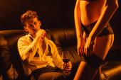 Fotografie selektiver Fokus des Mannes, der ein Glas Rotwein in der Hand hält und sexy Frau auf Schwarz ansieht