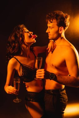curly woman in underwear biting fresh strawberry near shirtless man holding glass of champagne on black