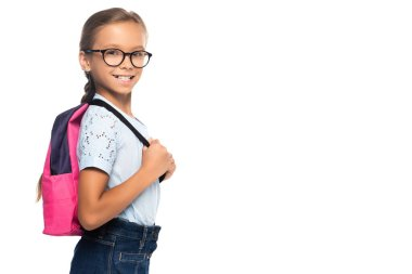Schoolgirl in glasses looking at camera and touching backpack isolated on white stock vector