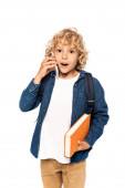 shocked and blonde schoolboy holding book and talking on smartphone isolated on white