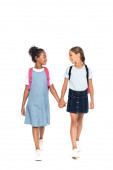 multicultural schoolgirls with backpacks holding hands and looking at each other isolated on white
