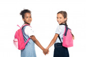 multicultural friends with backpacks holding hands and looking at camera isolated on white