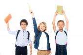 kudrnatí školáci a školačka drží knihy nad hlavami izolované na bílém