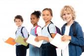 szelektív fókusz multikulturális iskolások hátizsákos gazdaság könyvek elszigetelt fehér