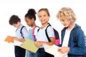 selektivní zaměření multikulturních školáků s batohy s knihami izolovanými na bílém