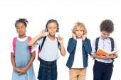 Fotografie multikulturelle Schulkinder hören Musik in drahtlosen Kopfhörern in der Nähe lockiger Junge lesen Buch isoliert auf weiß