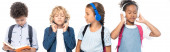 Fotografie panoramatický koncept školačky poslechu hudby a při pohledu na chlapecké čtení knihy v blízkosti multikulturní školáci izolované na bílém