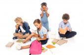 Fotografie Schulkinder sitzen neben Büchern, Äpfeln und afrikanisch-amerikanischen Kind in drahtlosen Kopfhörern isoliert auf weiß