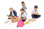 školáci sedí u knih, jablek a africké americké dítě v bezdrátových sluchátkách izolovaných na bílém