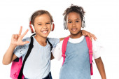 školák poslouchající hudbu v bezdrátových sluchátkách, objímající afrického amerického přítele a ukazující tři prsty izolované na bílém