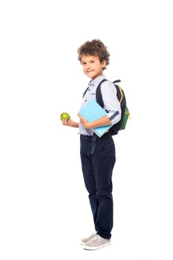 Curly schoolboy with backpack and book holding apple isolated on white stock vector