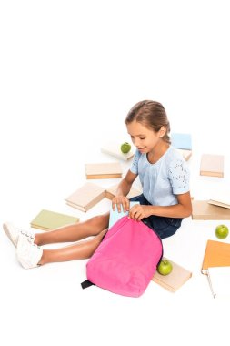 Schoolkid sitting near apples and putting book in backpack isolated on white stock vector