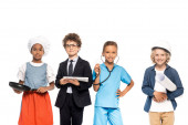 multicultural kids dressed in costumes of different professions holding blueprint, frying pan, stethoscope and digital tablet isolated on white