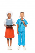 Photo multicultural kids in costumes of different professions holding frying pan and stethoscope while standing isolated on white