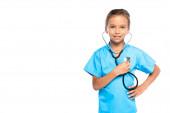dítě v kostýmu lékaře držícího stetoskop při stání s rukou na boku izolované na bílém
