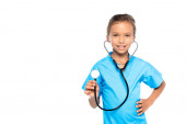 kid in costume of doctor holding stethoscope while standing with hand on hip isolated on white