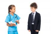 dítě v kostýmu lékaře ukazující rukou na digitální tablet poblíž kudrnatého chlapce ve formálním oblečení izolovaném na bílém