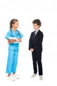 Kind im Arztkostüm hält digitales Tablet in der Nähe lockigen Jungen in formaler Kleidung isoliert auf weiß