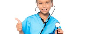 Panoramic shot of kid in costume of doctor holding stethoscope while showing thumb up isolated on white stock vector
