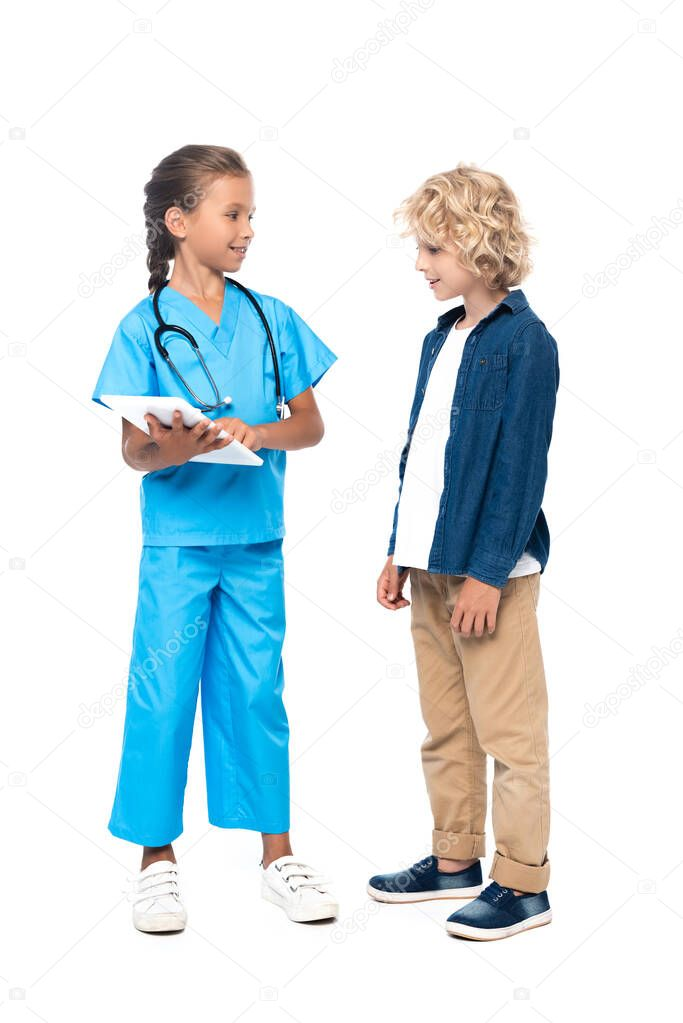 Child in costume of doctor using digital tablet near curly boy isolated on white stock vector