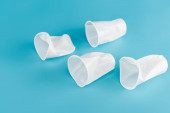 disposable plastic crumpled cups on blue background