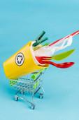 žlutý koš na recyklaci s plastem v malém nákupním košíku na modrém pozadí